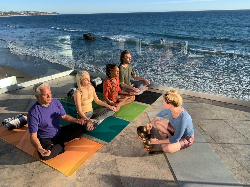 Navazon Digital's corporate video shoot cast doing group yoga on a balcony by the beach.