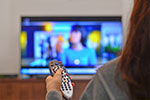 woman holding the remote in front of a tv.