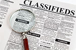 "newspaper that has ""Classified"" as the headline with a magnifying glass on top."