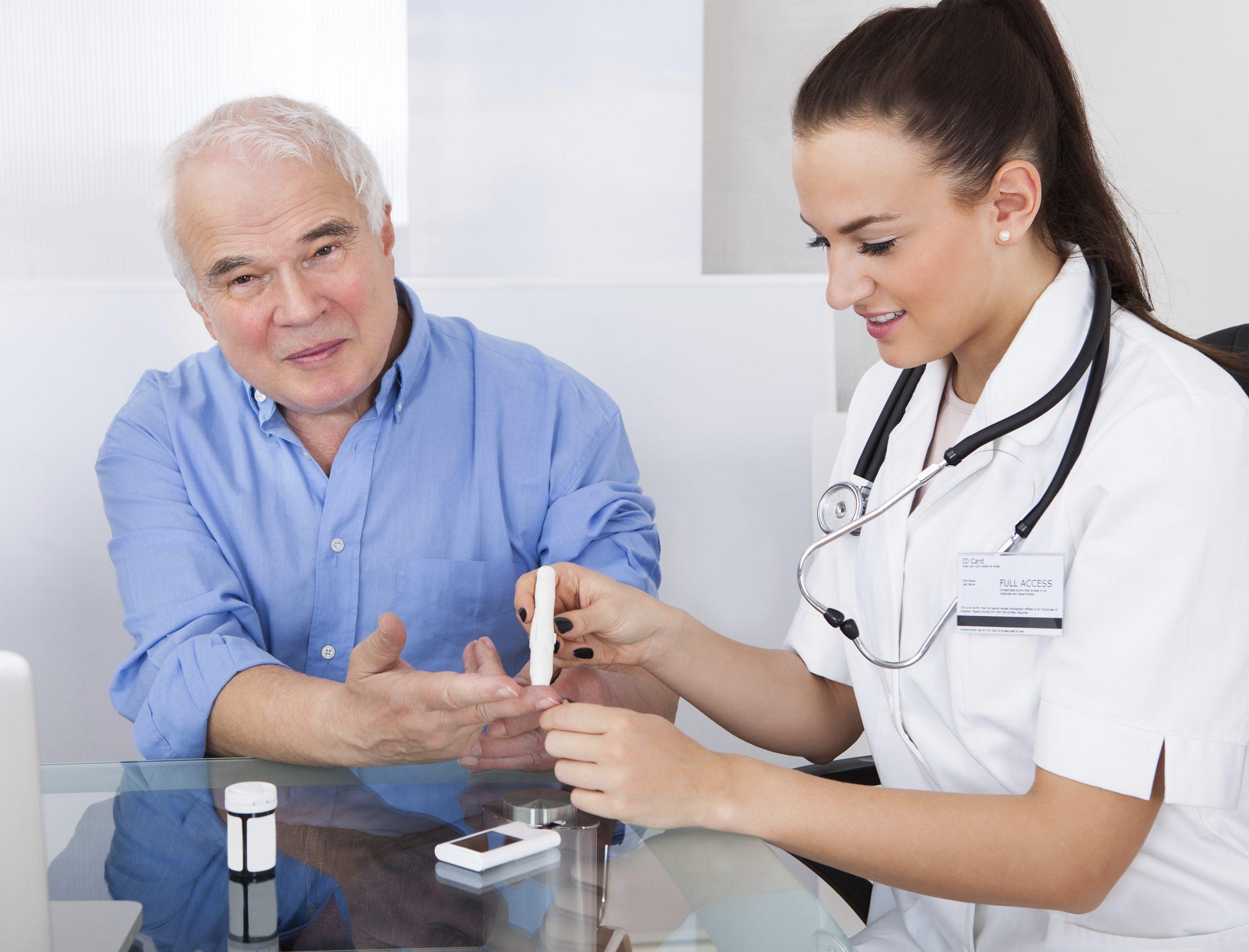 Nurse pricking a senior mans finger